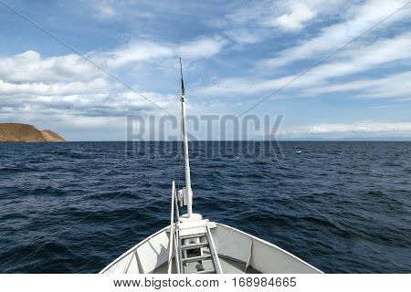 View from the bow of a ship with boundless navy blue water and beautiful white clouds