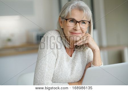Senior woman at home websurfing on laptop computer