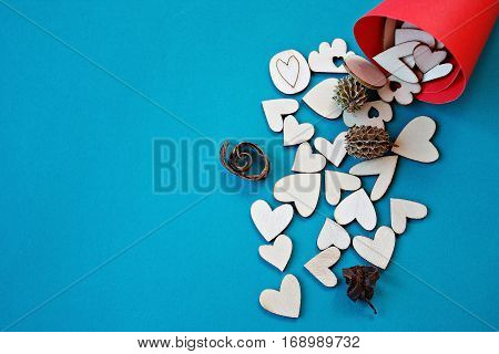 Valentines day or love concept : Wooden hearts in a red craft paper cornet on blue background