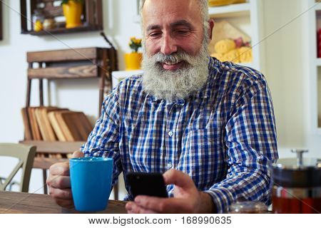 Close-up of mature man with a cup of tea. Male using telephone, texting with friends. Wearing checked shirt. Kitchen interior, a bookshelf standing behind