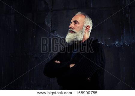 A mid right side-view shot from below of handsome elderly bearded man with folded arms on the breast. Looking away while standing against the black background