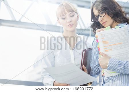 Mid-adult businesswoman showing document to female colleague in office