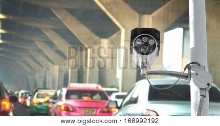 Security camera equipment and traffic concept - Security camera equipment on pole in morning traffic jam under high way and copyspace