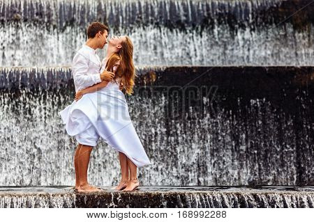 Happy family on honeymoon holidays - married loving couple hugging kissing with fun under falling water in cascade waterfall pool. Active lifestyle people travel on summer vacation on Bali island.