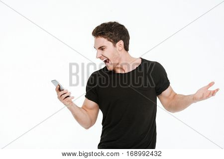 Picture of screaming young man dressed in black t-shirt standing over white background using phone.