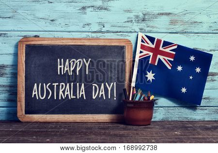 a chalkboard with the text happy Australia Day written in it, a pot with pencils and the flag of Australia, on a wooden surface, against a rustic blue wooden background