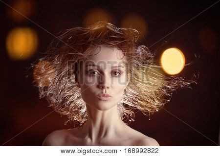 beautiful woman with flying wet hair on black background with blurred lights