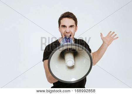 Picture of young aggressive man dressed in black t-shirt standing over white background screaming with mouthpiece.