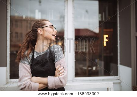 Photo of happy young woman confectioner with long hair standing with arms crossed near cafe outdoors. Look aside.