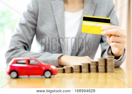Businesswomen hand with credit card and many coins with car
