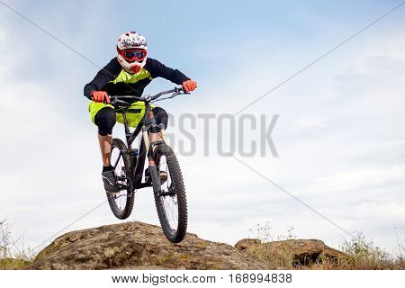 Professional Cyclist Jumping over Rock on the Mountain Bike on the Rocky Hill. Extreme Sport Concept. Free Space for Text.