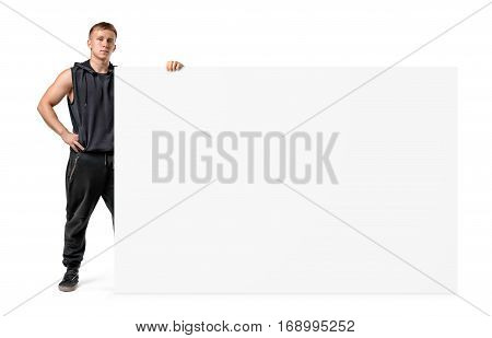Muscular young man in sportswear is holding a side of a huge blank banner isolated on white background. Sport and health. Keep fit. Advertising and promotion