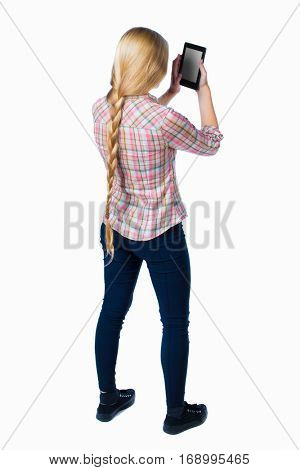 back view of standing young beautiful  girl with tablet computer in the hands of. girl  watching. Isolated over white background. Long-haired blonde in a checkered shirt looking into e-book reader