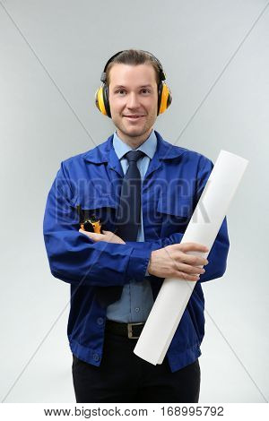 Handsome engineer with headphones, drawing and portable radio transmitter on light background
