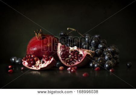 still life of pomegranate and grapes in the dark room