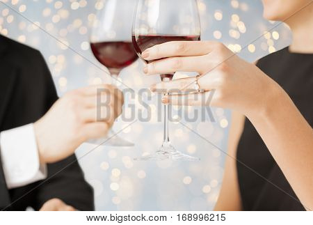 people, holidays, proposal, engagement and celebration concept - close up of engaged couple hands with ring and red wine glasses over lights background