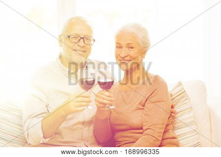 family, holidays, drinks, age and people concept - happy senior couple with glasses of red wine at home