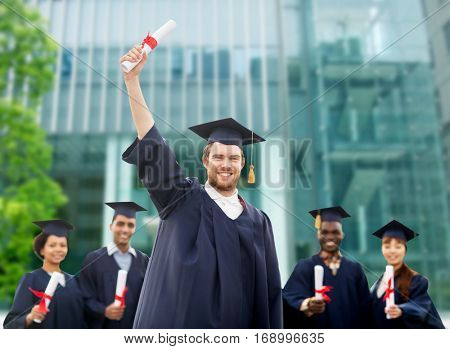 education, graduation and people concept - group of happy international students in mortar boards and bachelor gowns with diplomas over university building background
