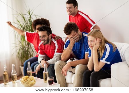 people, leisure, rivalry and sport concept - happy friends or football fans drinking beer and watching soccer game or match at home