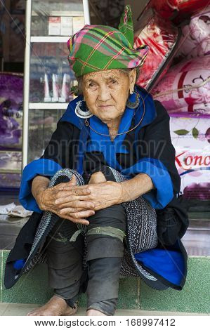 Yen Bai, Vietnam - Sept 22, 2012: Portrait of Hmong old woman sitting on Nga Ba Kim market. The Hmong are an Asian ethnic group from the mountainous regions of China, Vietnam, Laos, and Thailand