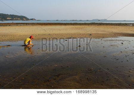 Quang Ninh, Vietnam - May 1, 2012: A boy working on beach when tide going out, rake black sand to catch sell fish. There are a lot of children labors in country