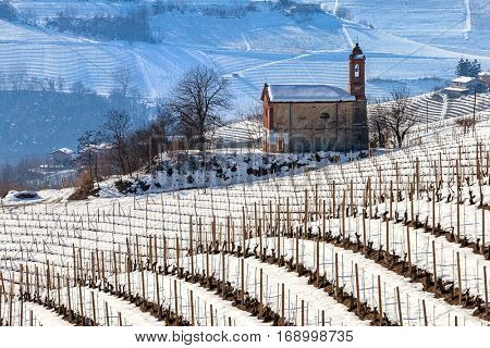 Small parish church among wintry vineyards on snowy hills in Piedmont, Northern Italy.