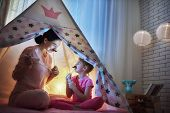 Happy loving family. Young mother and her daughter girl play in children room at the bedtime. Funny mom and lovely child are having fun with flashlights indoors.  poster