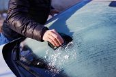 Man scraping ice from the windshield of a car poster