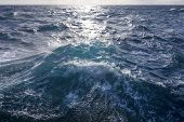Wind-fueled surface waves of ocean create choppy turbulence as sunlight reflects brightly on stormy surface poster