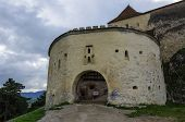 Gate tower of medieval fortress in Rasnov with mountains at background Transylvania Brasov Romania poster