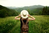 woman traveler with backpack holding hat and looking at amazing mountains and forest wanderlust travel concept space for text atmosperic epic moment poster