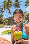 Beautiful Asian bikini woman drinking fresh coconut water directly from fruit with straw on beach. Multiracial girl smiling at camera portrait with perfect teeth sipping on hydration juice food. poster