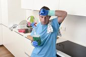 young lazy house cleaner man washing and cleaning the kitchen with detergent spray bottle and sponge in stress and desperate face expression in male housework and housekeeping concept poster