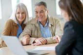 Senior couple meeting financial adviser for investment                 poster