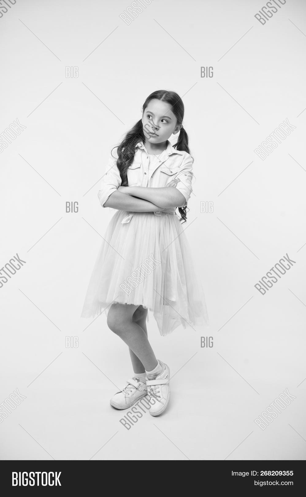 00a2cadf9859f Child keep arms crossed on yellow background. Little girl pose with serious  look in fashion wear. She is so cute. Her perfect style. Innocent beauty.
