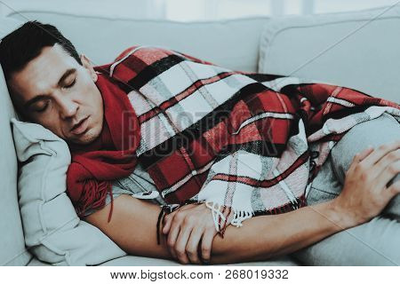 Man With Cold Resting On Sofa In Checkered Blanket. Man At Home. Sick Young Man. White Sofa In Room.