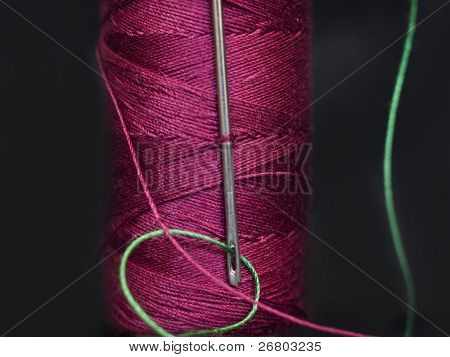 needle in the red bobbin with green yarn