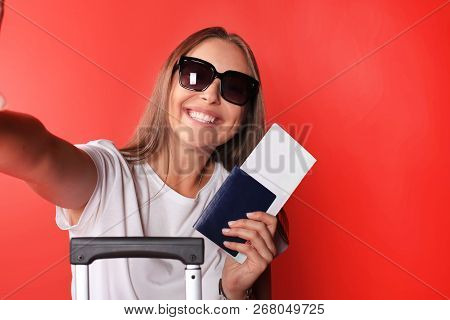 Smiling Woman Taking A Selfie With Sunglasses While Holding Passport With Red Suitcase, Isolated On