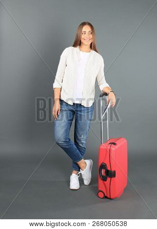 Young Tourist Girl In Summer Casual Clothes, With Red Suitcase, Passport, Tickets Isolated On Grey B