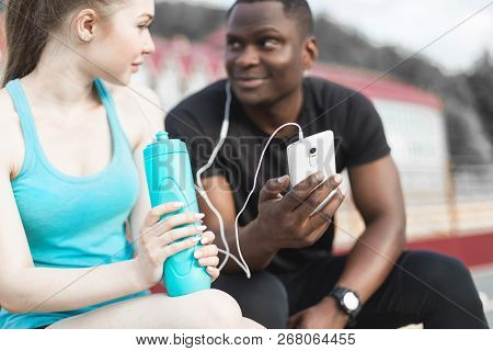 Group Of Athletes Sitting On The Bench And Resting After Hard Street Workout Session. Man And Woman