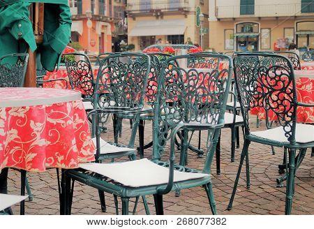 Italian Café Scene. Chairs And Tables Outside A Stylish Outdoor Cafe On Piazza Garibaldi In Menaggio