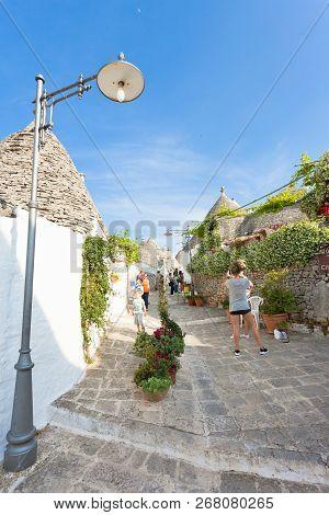 Alberobello, Apulia, Italy - June 1, 2017 - Tourists Walking Up A Traditional Street In Alberobello