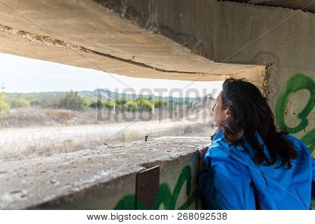 A Young Woman Is Looking Through The Embrasure In A Concrete Security Separation Fence On The Border