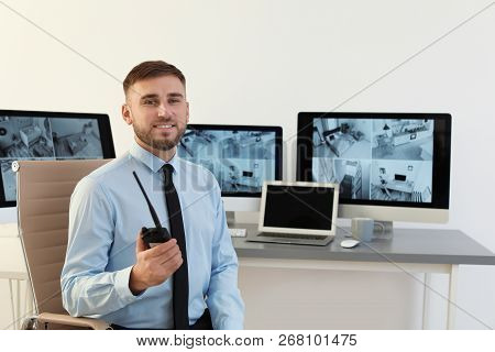 Male Security Guard With Portable Transmitter At Workplace