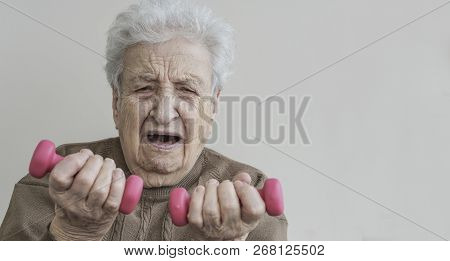 A Senior Woman Has Difficultly Lifting The Dummbels