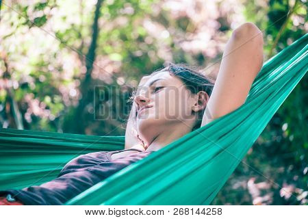 The Girl Is In A Hammock. Woman Resting Lying In A Green Fabric Hammock. Rest In The Woods.