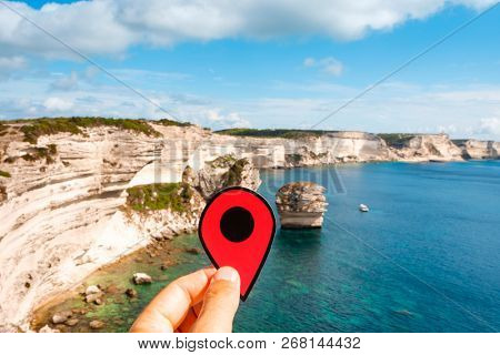 closeup of the hand of a caucasian man holding a red marker at the cliffs over the Mediterranean sea in Bonifacio, Corse, in France