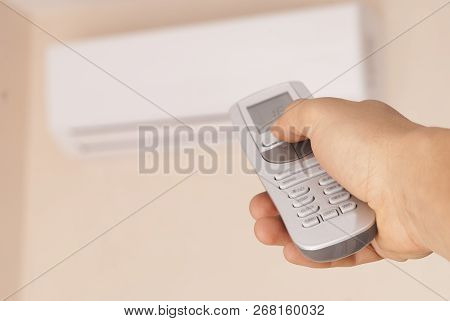 Man Holds In His Hand The Remote Control For The Air Conditioner