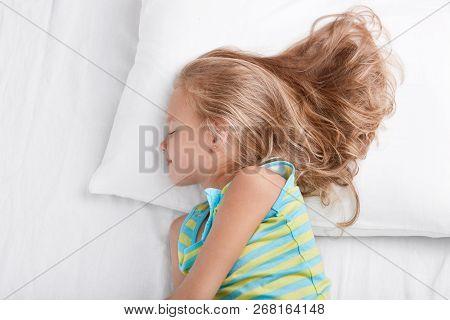 Sideways Shot Of Small Kid Wears Nightwear, Being Deep In Sleep, Rests At Bed, Lies On White Bed, En