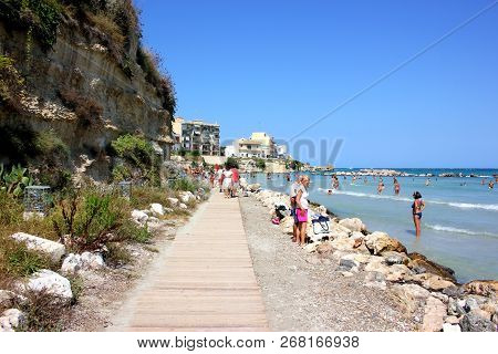 Otranto, Italy - August 28, 2018: Local People And Tourists On The Beach In Front Of The Historic Ce